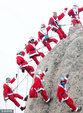 韩登山爱好者扮圣诞老人惊险攀岩_环球动态