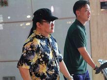 刘欢梳长马尾现身机场 身穿花衬衫表情严肃